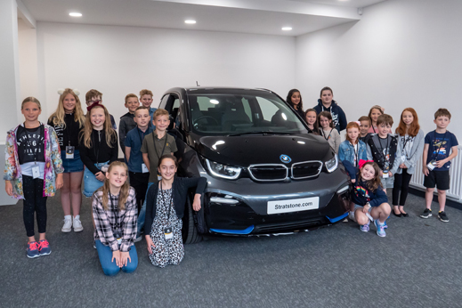 Children of Pendragon Employees stood around a black BMW.