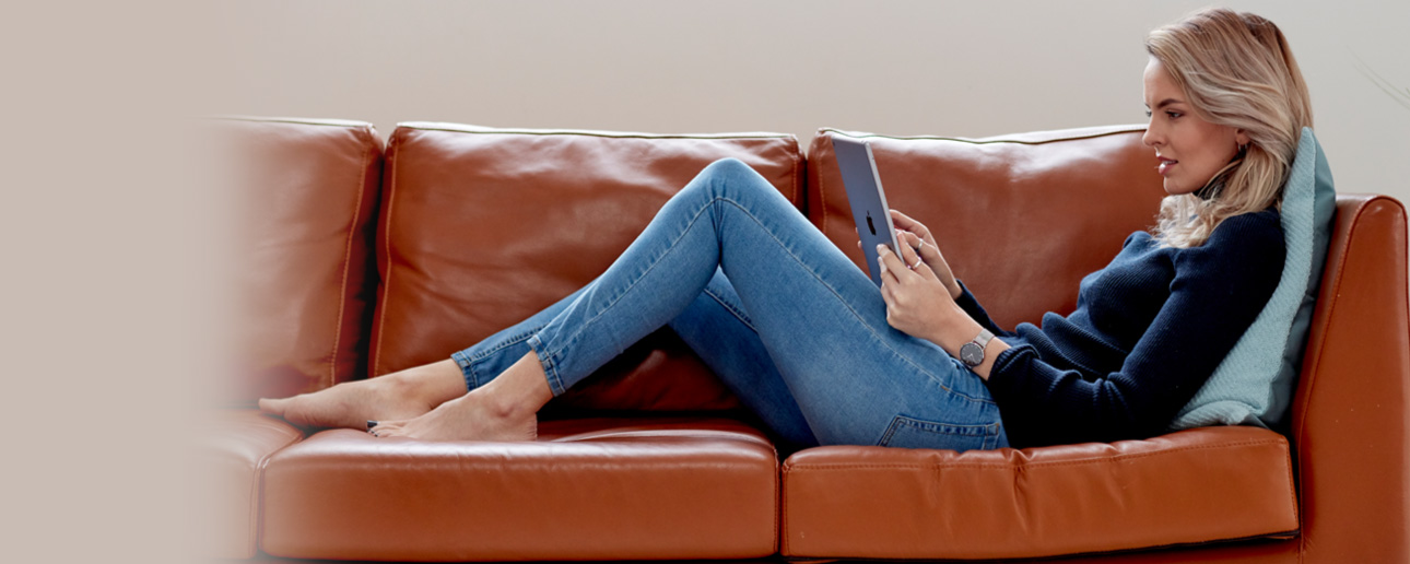 Woman on her tablet sat on a sofa.