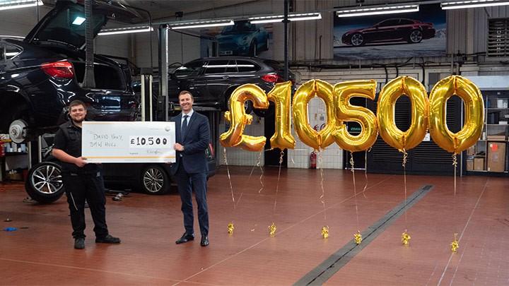 David Uney holding his bonus cheque at Stratstone BMW.